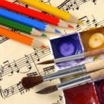 color pencils and paints with brushes on the musical notes background